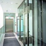 Fahrstuhl und Fluchttüre aus Glas und Stahlkonstruktion