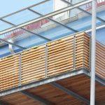 Balkon aus Metall mit Holzverkleidung und Glasüberdachung